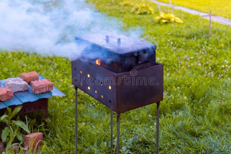 Fumeiro caseiro no fogo O fogo queima-se sob uma caixa do metal para fumar, estando na grade Método de fumo imagem de stock royalty free