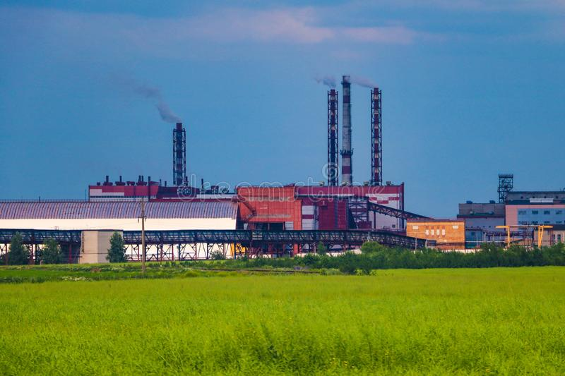 Fumes of a mining plant against the sky and green grass.  royalty free stock image