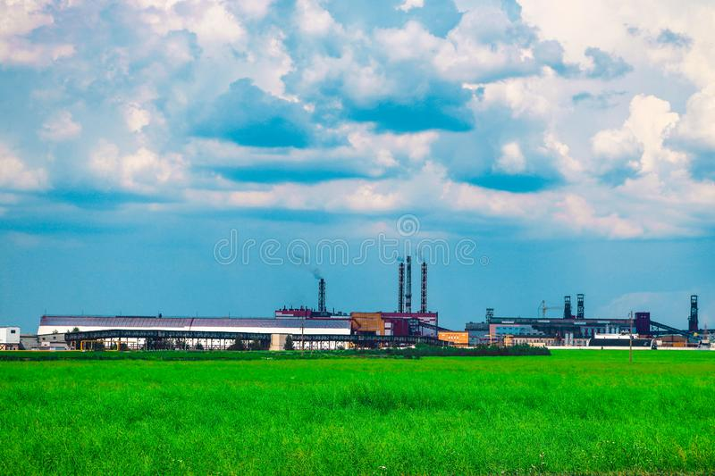 Fumes of a mining plant against the sky and green grass.  stock photography