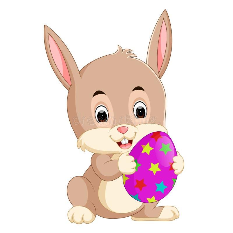 Fumetto poco coniglietto che tiene l'uovo di Pasqua illustrazione di stock