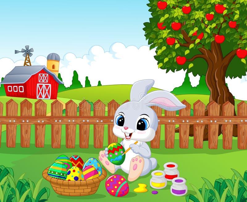Fumetto sveglio del coniglietto di pasqua che dipinge un uovo nel giardino illustrazione di stock