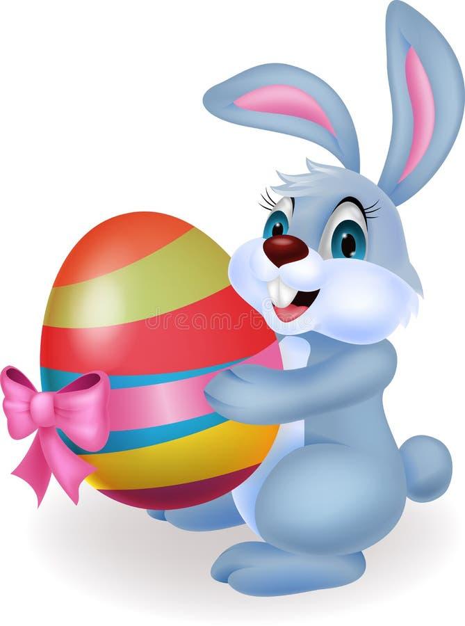 Fumetto sveglio del coniglio che tiene l'uovo di Pasqua illustrazione di stock