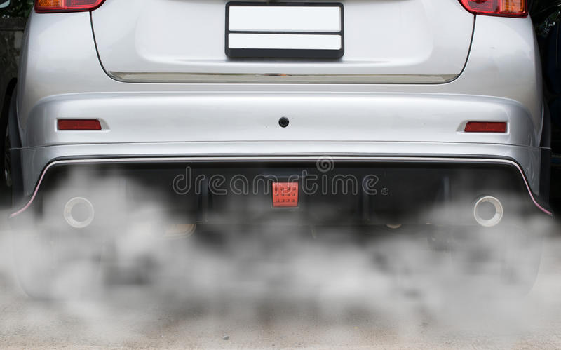 Fumi da un'automobile producendo l'inquinamento, scarico del tubo dell'automobile del fumo immagini stock