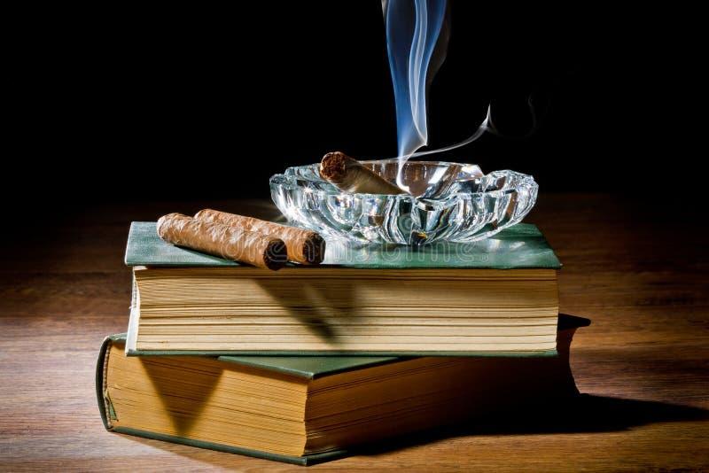 Fumi dal sigaro con il portacenere e due libri fotografia stock