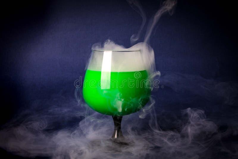 Fumi nel vetro di cocktail su un fondo nero Fondo della pozione della strega per Halloween Bevanda insolita della barra immagini stock
