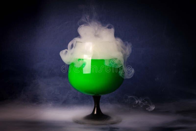 Fumi nel vetro di cocktail su un fondo nero Fondo della pozione della strega per Halloween Bevanda insolita della barra immagini stock libere da diritti