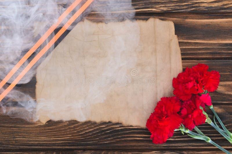 fumi sopra il nastro di St George, la vecchia carta vuota ed i garofani su superficie di legno immagine stock