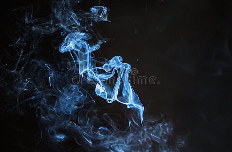 Fumo azul no fundo preto imagem de stock