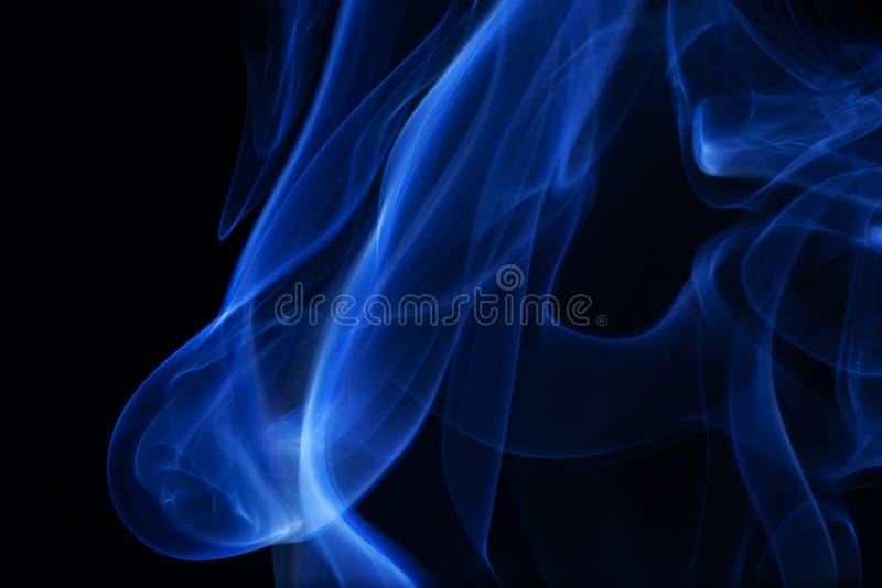 Fumo azul sobre o fundo preto. foto de stock