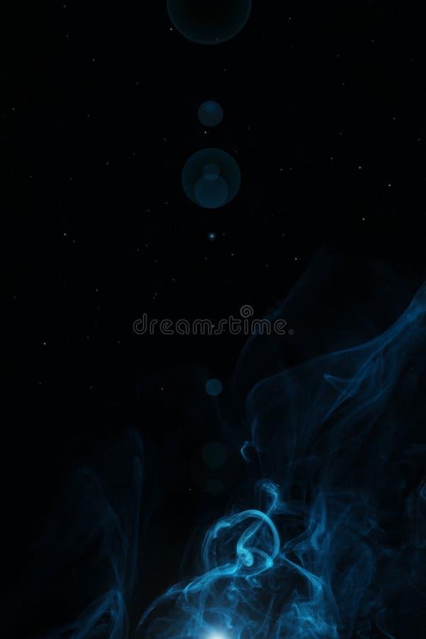 fumo blu di turbinio con luce su fondo nero fotografia stock