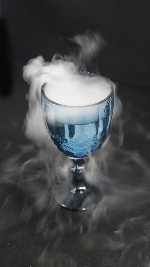 Fumo branco que flui de um copo de vidro imagens de stock
