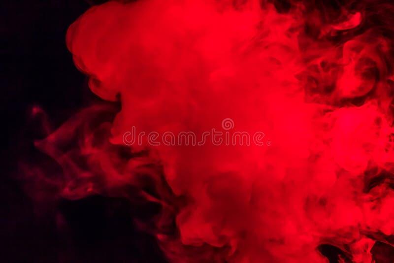 Fumo colorido em um fundo preto de cores vermelhas e brancas Th fotografia de stock