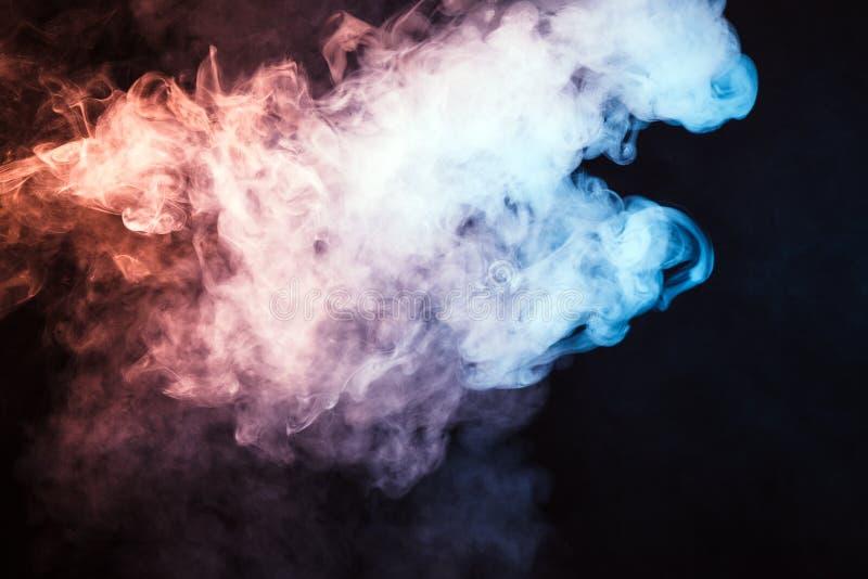 fumo colorido em um fundo preto O conceito da mostra clara a foto de stock royalty free