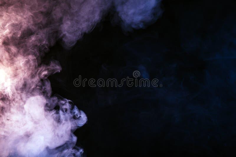 fumo colorido em um fundo preto O conceito da mostra clara a fotos de stock