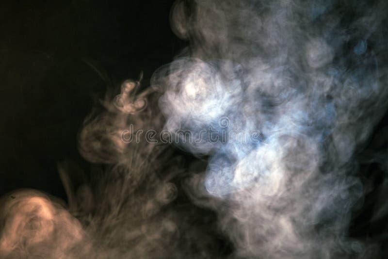 fumo colorido em um fundo preto O conceito da mostra clara a imagem de stock royalty free