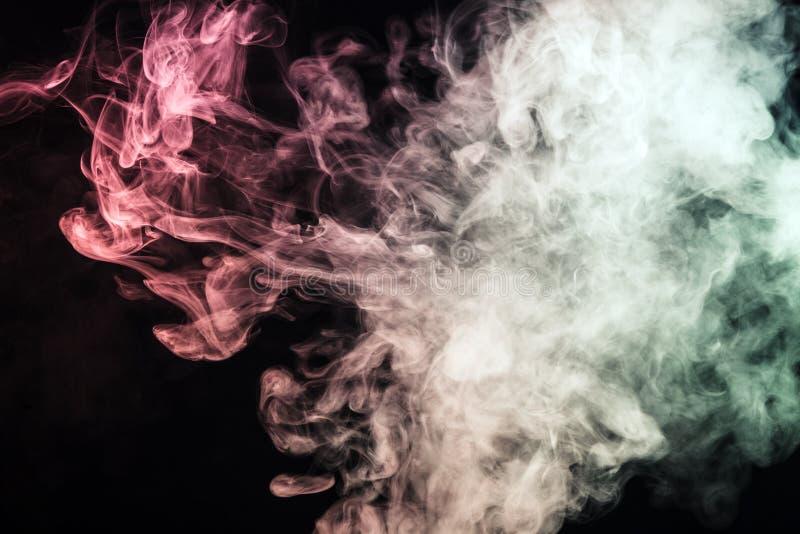 fumo colorido em um fundo preto O conceito da mostra clara a fotos de stock royalty free