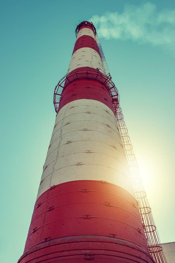 Fumo da un camino della fabbrica contro un cielo blu Vista verticale fotografia stock libera da diritti
