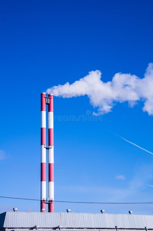 Fumo de duas tubulações contra o céu azul fotos de stock
