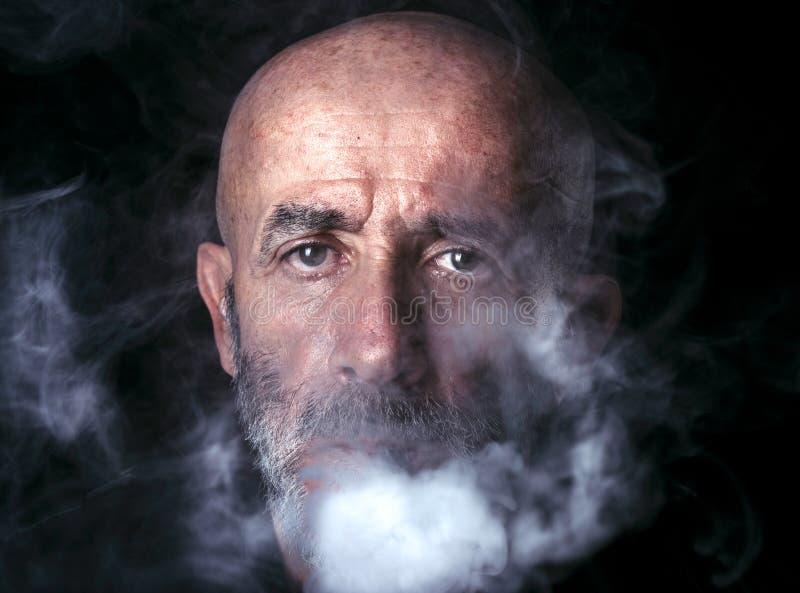 Fumo de sopro do homem fotografia de stock