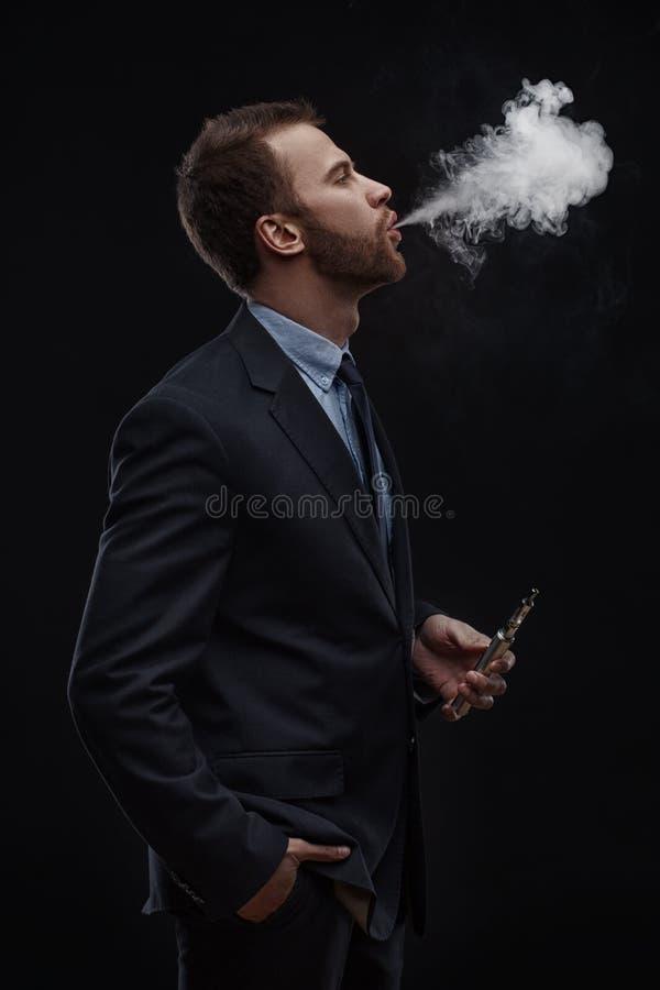 Fumo de sopro do homem de negócio do cigarro eletrônico imagens de stock