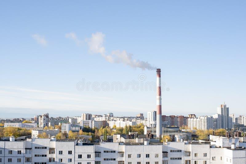 Fumo de uma tubulação de uma sala de caldeira na cidade com o começo de uma estação de aquecimento fotografia de stock royalty free