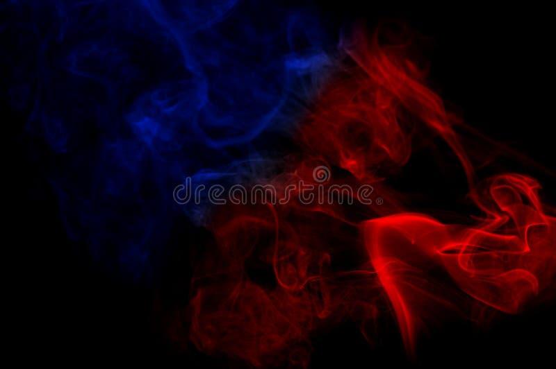 Fumo di colore come forma astratta nell'aria su fondo nero fotografia stock
