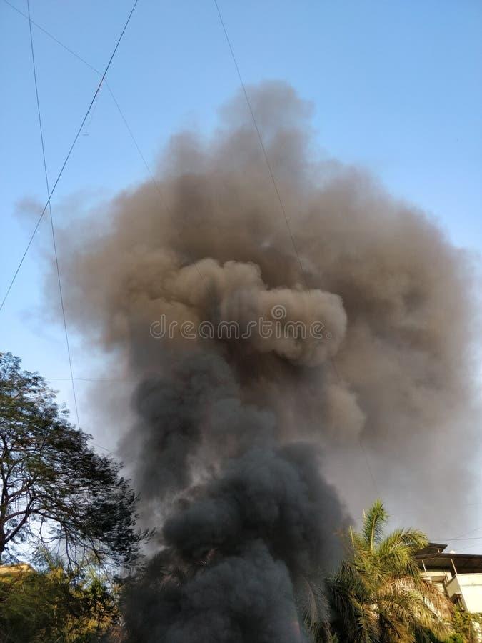 Fumo nero che esce da una costruzione sul fuoco fotografia stock