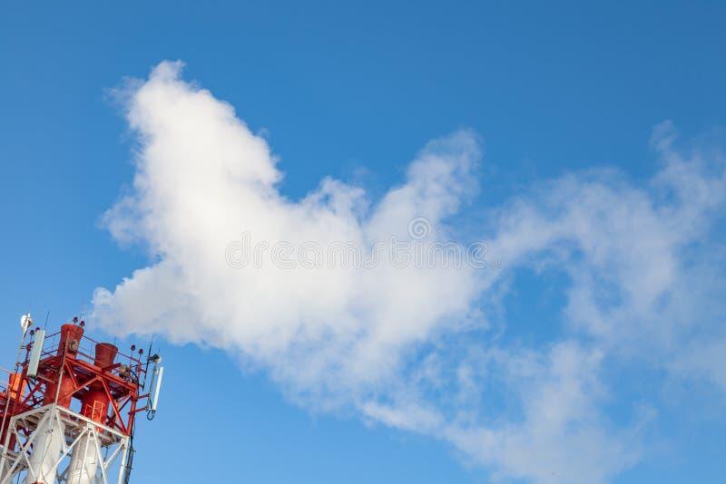 Fumo nocivo bianco che esce dai tubi bianchi rosso e con le antenne di comunicazione su mezzi mobili ad una fabbrica nel centro u fotografie stock libere da diritti