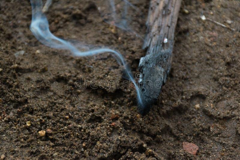 Fumo que aumenta da parte de madeira queimada fotografia de stock