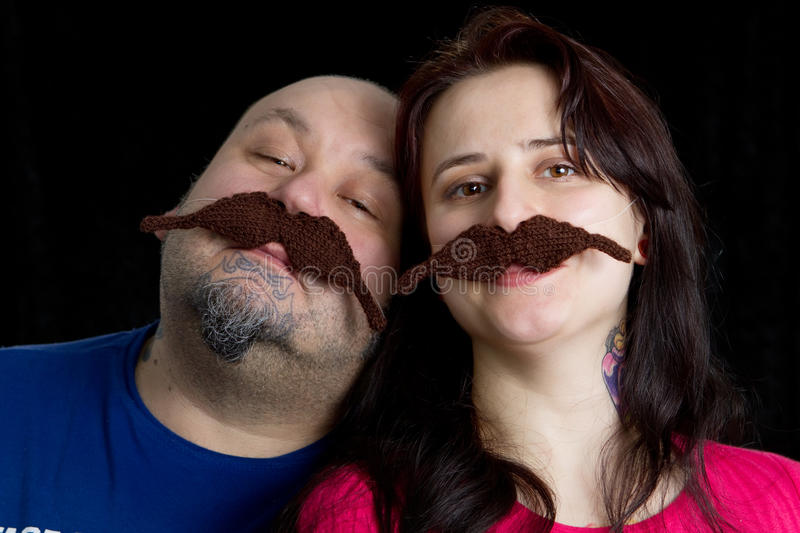 Fun. The couple wearing fake moustache against black background royalty free stock photo