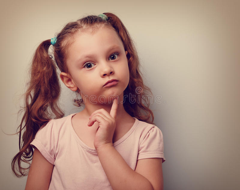Fun annoyed kid girl thinking and looking serious about. Closeup. Vintage portrait stock images