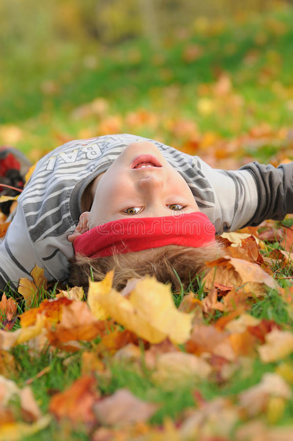 Fun in autumn. Young child with red headband lying on green grass with autumn colorful leaves, having fun and looking to the camera stock photos