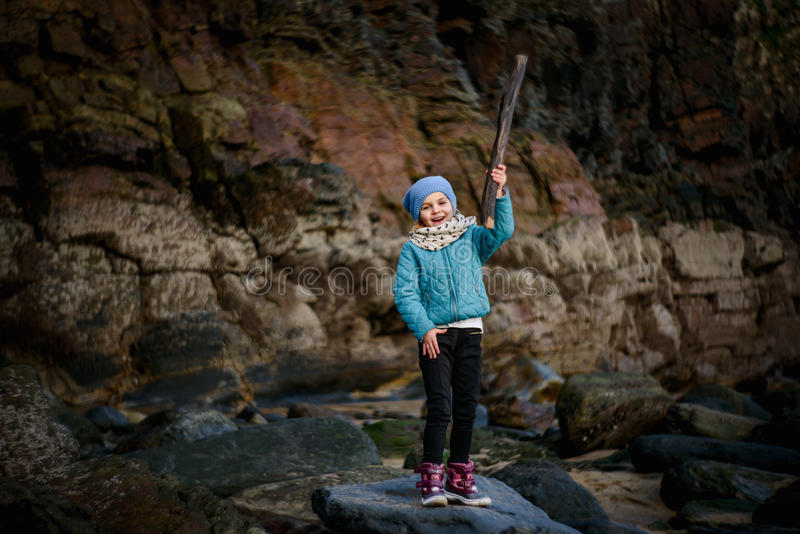 Fun at the Beach. A young girl smiling holding a stick at the beach royalty free stock photos
