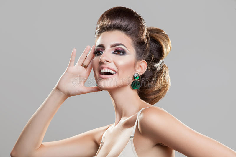 Fun beautiful young girl with creative hairstyle and professiona. L makeup looking away in studio stock photo