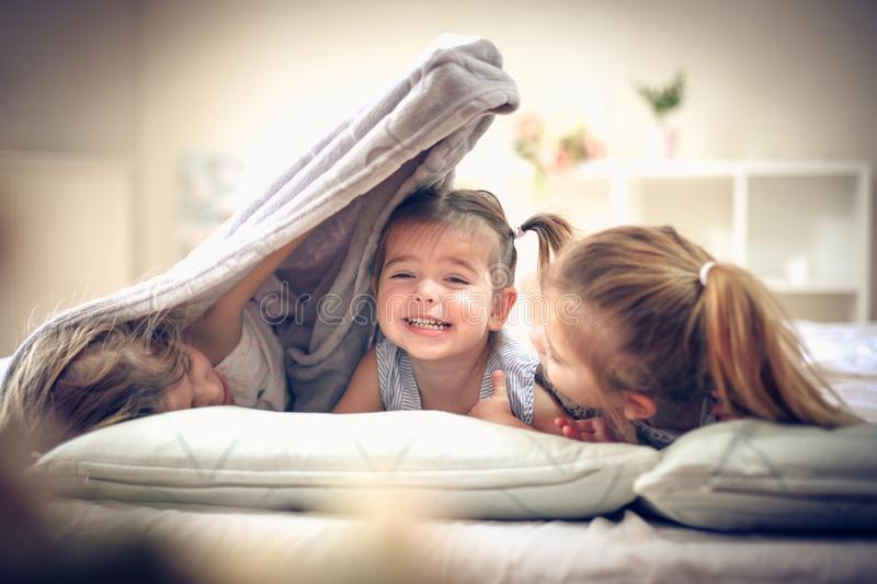 Fun in bed. Little girls playing in bed. Space for copy royalty free stock images