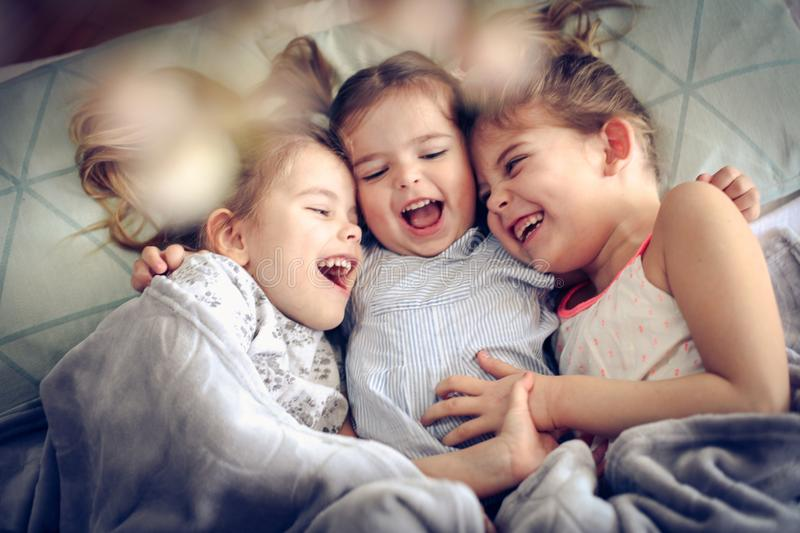 Fun in bed. Three little girls lying in bed and playing. Space for copy stock photos