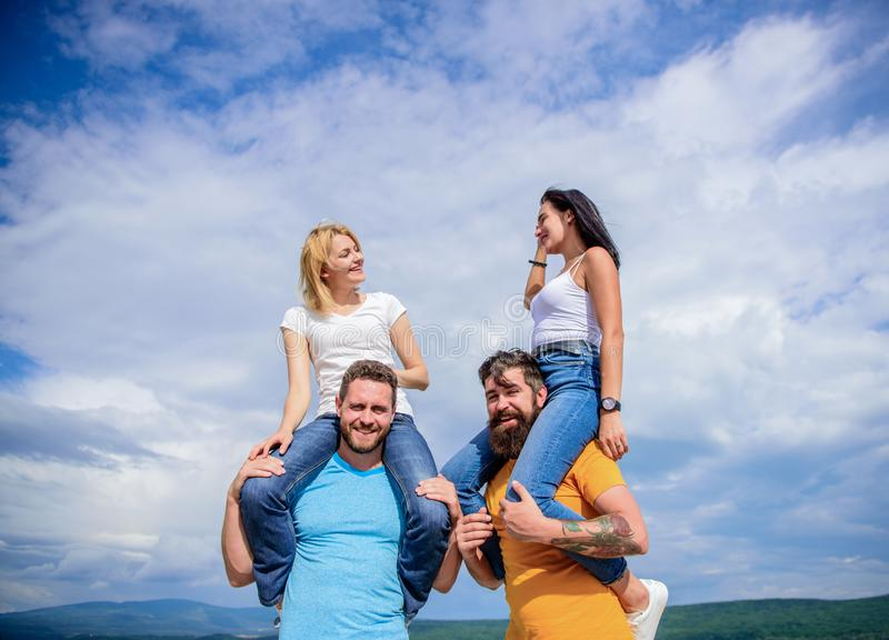 The fun begins. Loving couples enjoy fun together. Playful couples in love smiling on cloudy sky. Happy men piggybacking. Their girlfriends. Loving couples royalty free stock photography