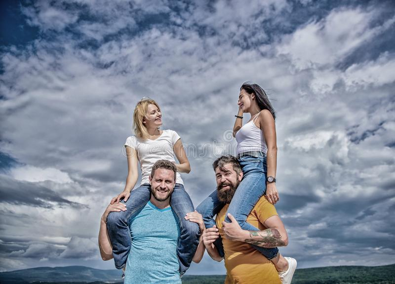 The fun begins. Loving couples enjoy fun together. Playful couples in love smiling on cloudy sky. Happy men piggybacking. Their girlfriends. Loving couples stock image
