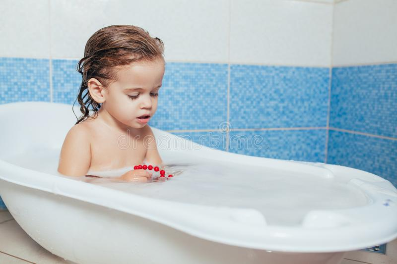 Fun cheerful happy toddler baby taking a bath playing with foam bubbles. Little child in a bathtub. Smiling kid in bathroom on stock photography