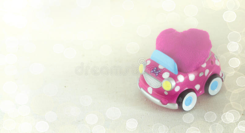 A fun children's toy car carrying a pink heart cushion. Valentine's day celebration concept. Bokeh background.  royalty free stock photography