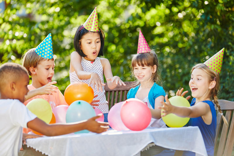 Fun at childrens birthday party. Kids have fun at childrens birthday party in summer in garden stock images