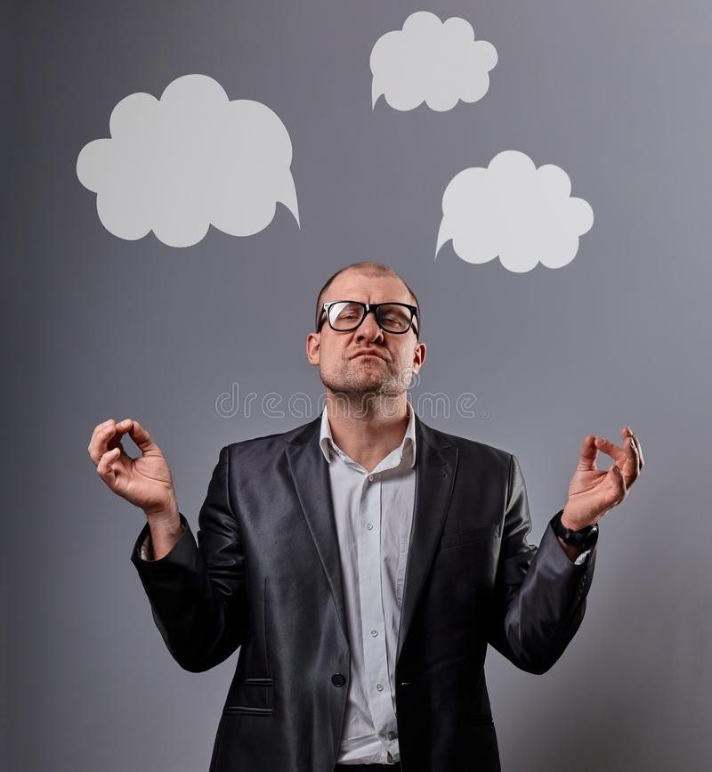 Fun comic bald business man in black fashion eyeglasses practicing the yoga and showing the zen sign with empty clouds above the royalty free stock image