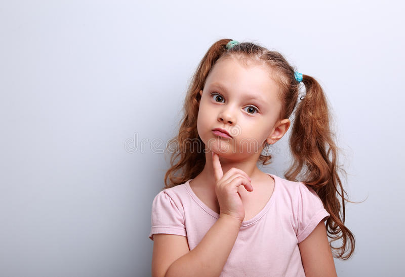 Fun confused kid girl thinking and looking serious about on blue stock photo
