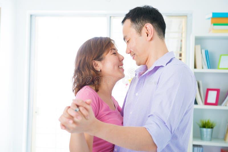 Fun couple dancing. Fun Asian couple dancing at home stock image