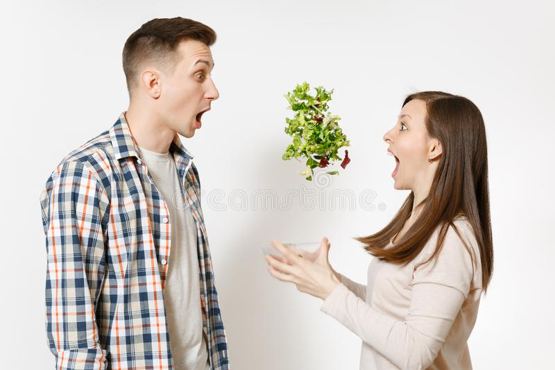 Fun couple man woman standing and throwing up salad from glass bowl isolated on white background. Proper nutrition. Fun couple men women standing and throwing up stock photo