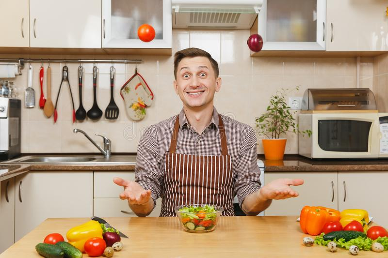 Handsome caucasian young man, sitting at table. Healthy lifestyle. Cooking at home. Prepare food. Fun crazy caucasian young man in apron, brown shirt sitting at stock photo