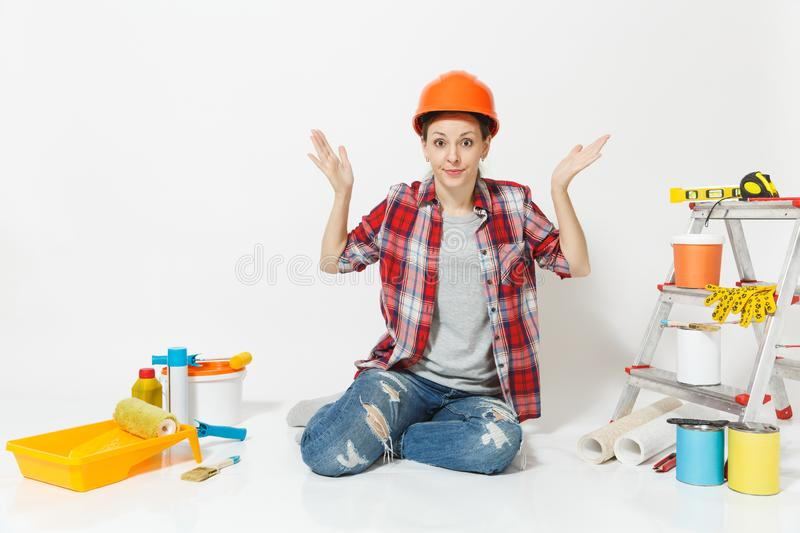 Fun crazy woman in orange protective helmet sitting on floor with instruments for renovation apartment isolated on white royalty free stock images