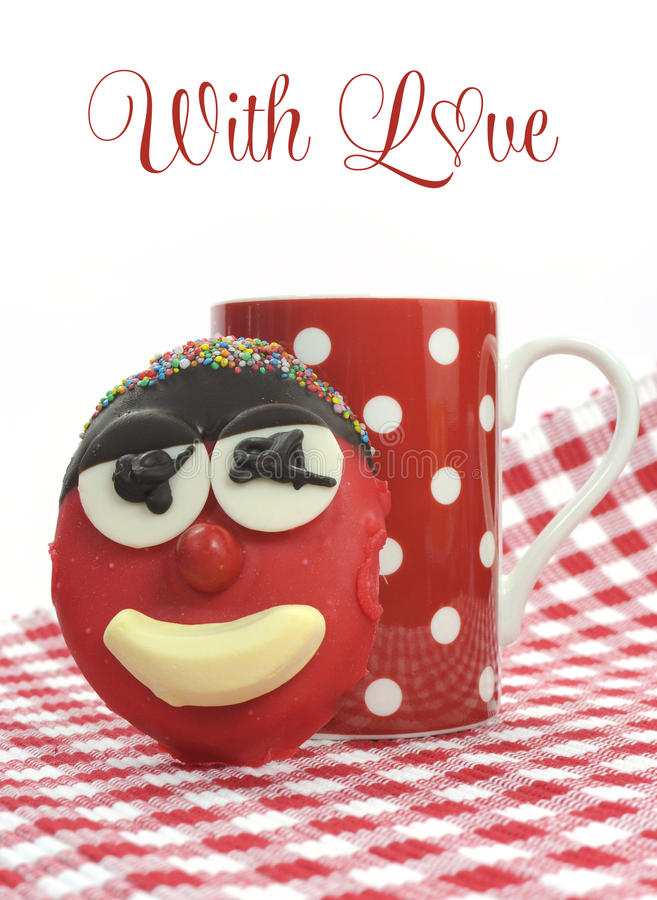 Fun cute childrens handmade cookie with candy face and red polka dot cup. Of tea or coffee for Mothers Day, birthday or Fathers day with sample text or copy royalty free stock photo