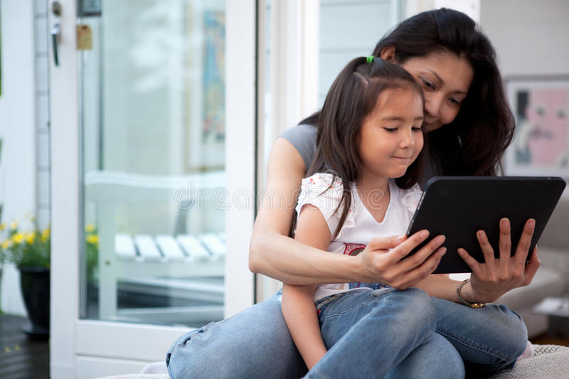 Fun with Digital Tablet. Mother and Daughter having fun on a digital tablet in a home interior