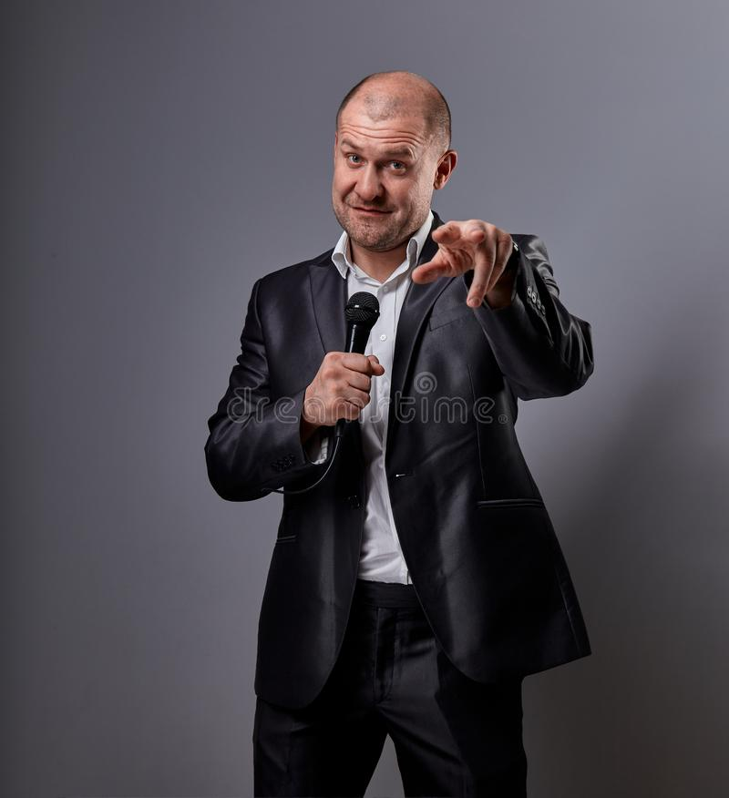 Fun emotional moving happy performer man presenting the show holding microphone in hand and showing the finger the choosing sign royalty free stock image